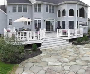 gray timbertech deck with flagstone patio patios
