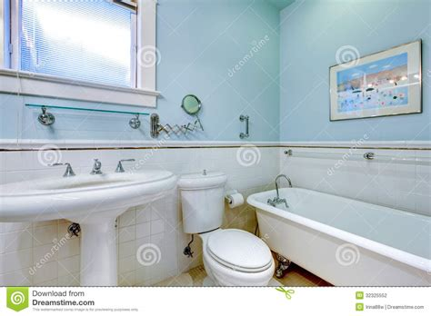 blue antique bathroom with white tub stock