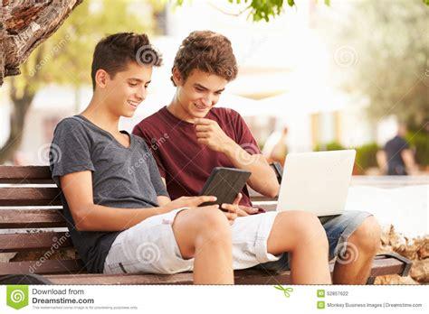 park bench digital teenage boys on park bench using laptop and digital tablet