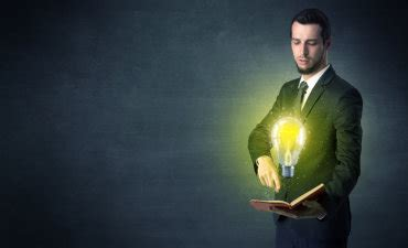 businessman holding book with lightbulb imposed © ra2