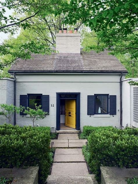 painted brick cottage home exterior with black shutters and yellow front door dwellings