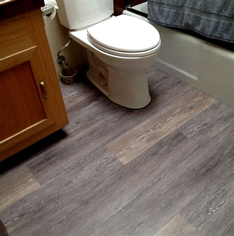 flooring interesting bathroom with white toilet and mocha wood vanity and coretec vinyl plank