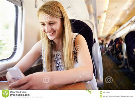 smiling girl using mobile phone in bed royalty free stock teenage girl using mobile phone on train journey stock