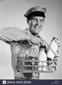 1950s 1960s smiling milkman in uniform looking at camera carrying two