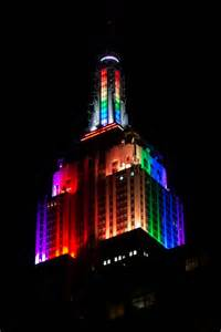 the empire state building lit up with rainbow colors in