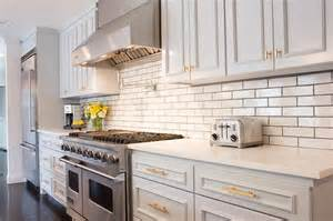 Light gray kitchen cabinets gold knobs pulls staggered kitchen