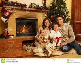 Family near fireplace in christmas decorated house interior with gift