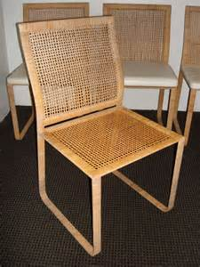Minimalist rattan dining chairs colored in brown with lush white