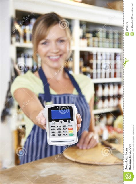 Cus Store Gift Card - sales assistant in food store handing credit card machine to cus stock photo image
