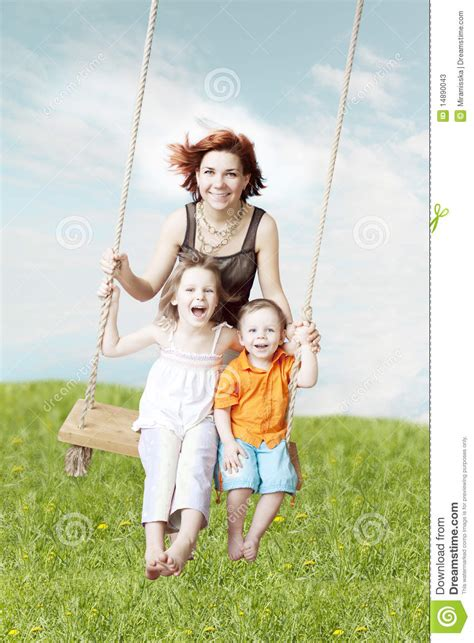 family swing family swing against the sky and grass stock photos
