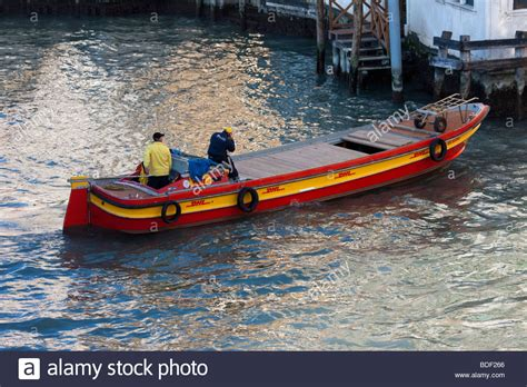 boat delivery red and orange dhl courier delivery boat on canal in