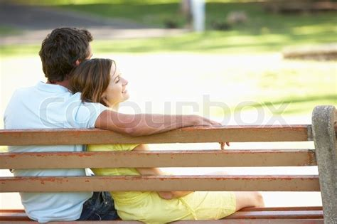 sitting on a park bench couple sitting together on park bench stock photo