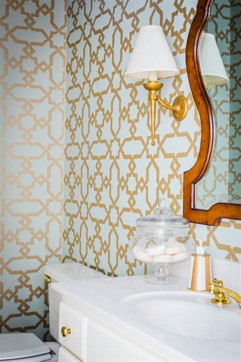 blue and gold bathroom wallpaper with white cabinet and