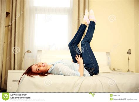 lying on my bed smiling woman lying on the bed with raised legs stock