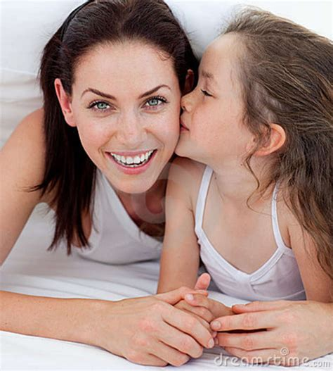 two girls kissing in bed little girl kissing her mother lying on bed royalty free
