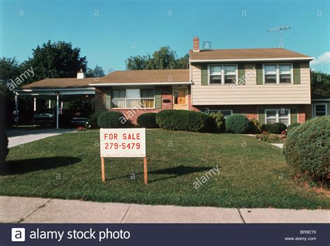 splitting the purchase of a secondary home 1960s 1970s split level suburban house with two cars in