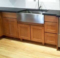 substantial wood kitchen island with apron sink single dark granite on island with stainless steel farm sink and