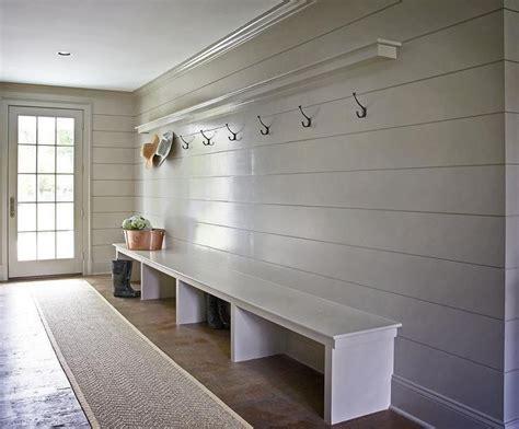 gray mudroom boasts gray shiplap walls lined   shelf