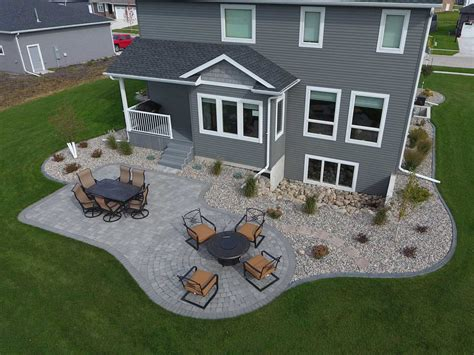 gray paver patio with edging rocks and plants oasis