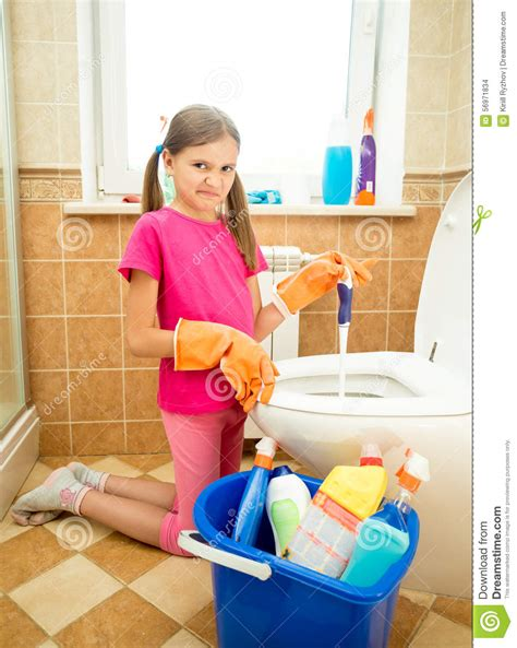 Girls Bathroom Sign cleaning toilet with disgust stock photo image