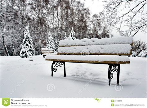 bench snow snow covered park bench royalty wreath covered in snow on park bench stock photo