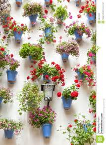 Spanish House Plans With Courtyard Blue Flowerpots And Red Flowers On A White Wall With