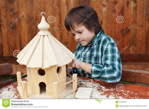 making a house little boy making the last finishing touches on a bird