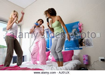 day one bedroom dancing teenage girl standing on her bed holding pom poms