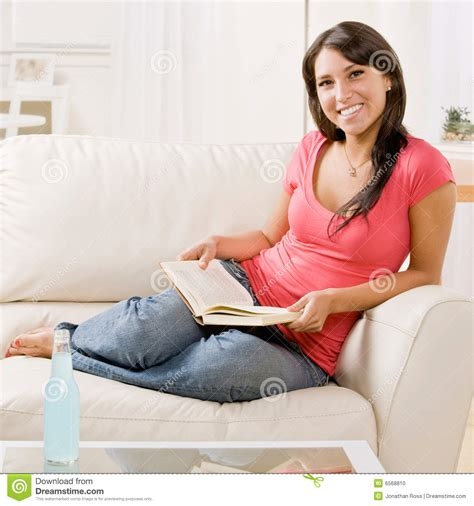 reading book on sofa at home stock photo