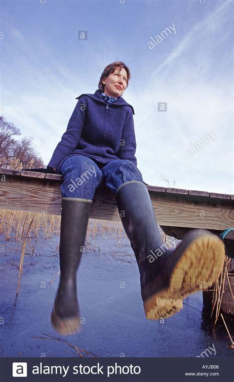 wearing rubber boots a wearing rubber boots sitting on a bridge