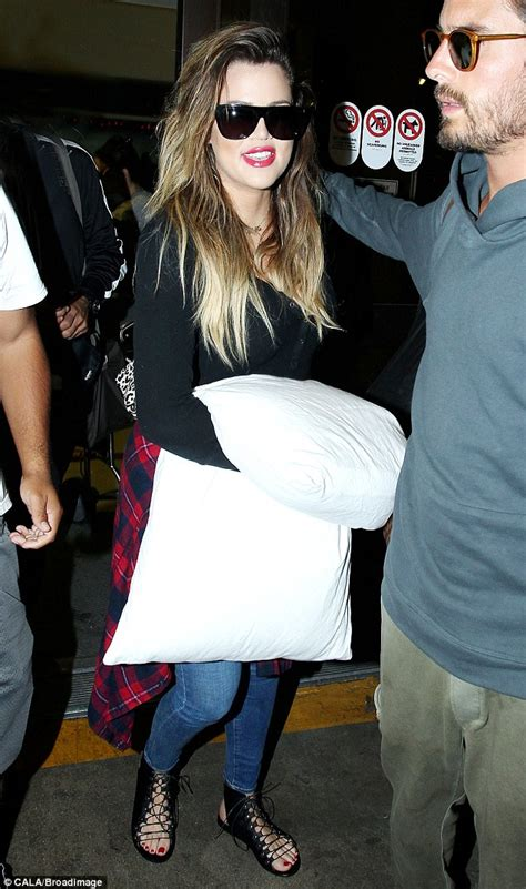 khloe clutches large pillow as she jets into