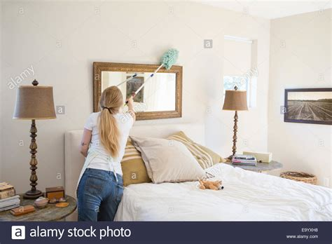 cleaning bedroom young woman cleaning bedroom with green cleaning products stock photo royalty free image