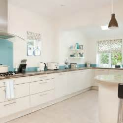 The bright blue glass splashback breaks up the white expanse of this