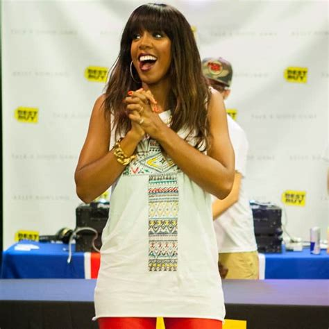kelly rowland in a white tank top highlighing derriere in kelly rowland s white tank red pants album signing look