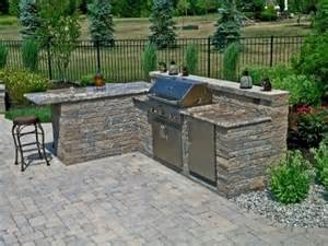 an outdoor kitchen with granite countertops compliment