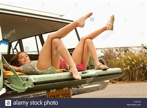 young teen legs spread laying down two girls lying in estate car with legs in the air stock