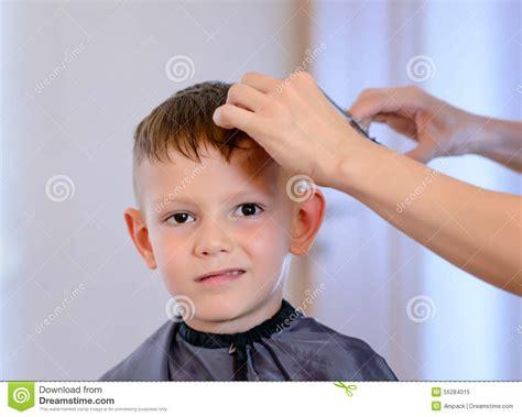 beauty salon boys hairdresser cutting a young boys hair stock photography