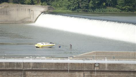 salvage boat work salvage crews work to retrieve boat that flipped over dam