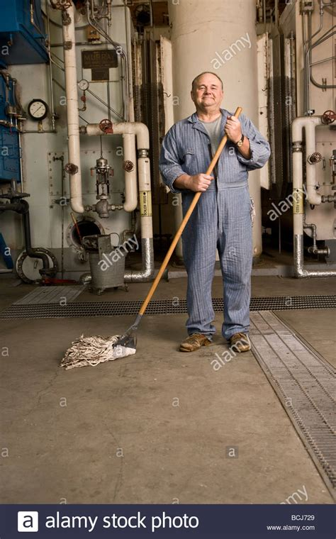 caucasian in blue custodian janitor overalls in factory setting stock photo royalty free