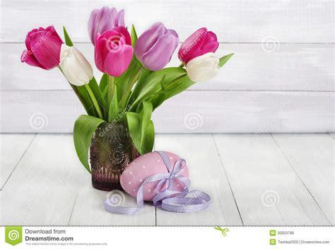 tulipani in vaso tulipani in un vaso di vetro con l uovo di pasqua immagine