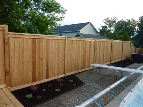 custom cedar wood privacy fence around pool built on top of retaining wall wood fence