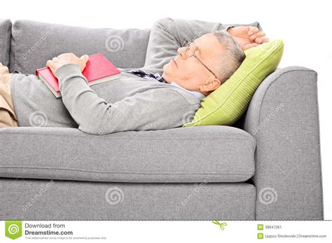 mature couch mature man sleeping on sofa and holding a book stock image