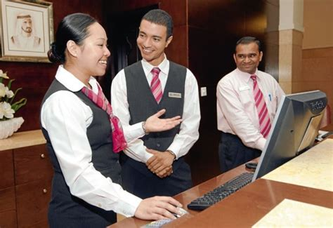 front desk agents with vests creating behind a desk