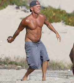 Kenny chesney reveals physique while paddleboarding with pro surfer