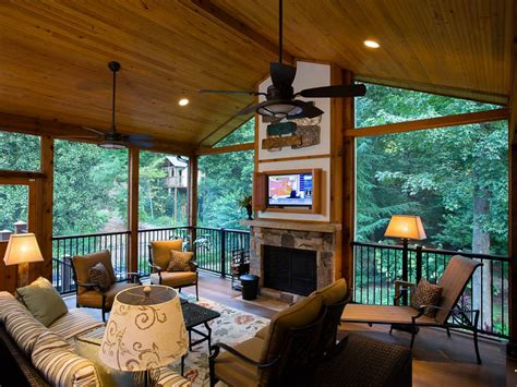 a rustic covered porch with a fireplace and tv screen