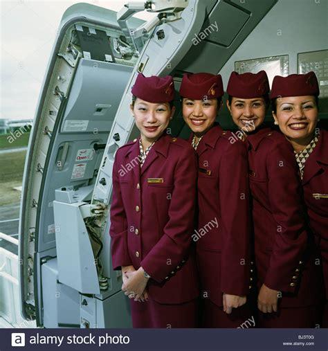 cabin crew members four cabin crew members wear the uniforms of qatar