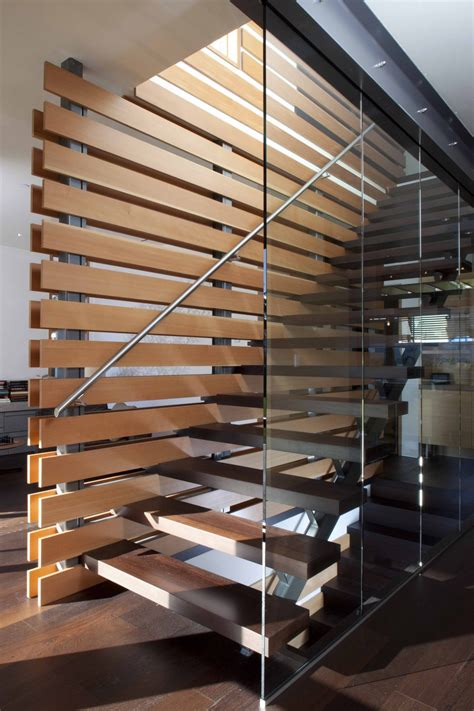 modern wood slat wall interior concrete staircase with wooden steps and glass
