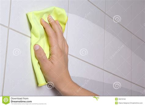 toilet rag hand with yellow rag cleaning the bathroom tiles stock