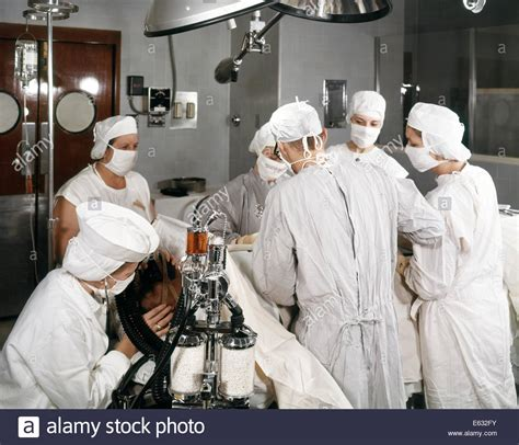 scrub in operating room 1960s operating room team with scrub and circulating two stock photo royalty free image