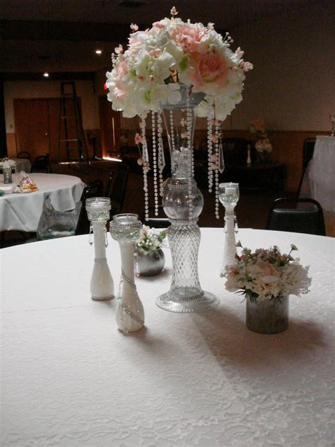 table centerpieces with blush lace overlays on white linen